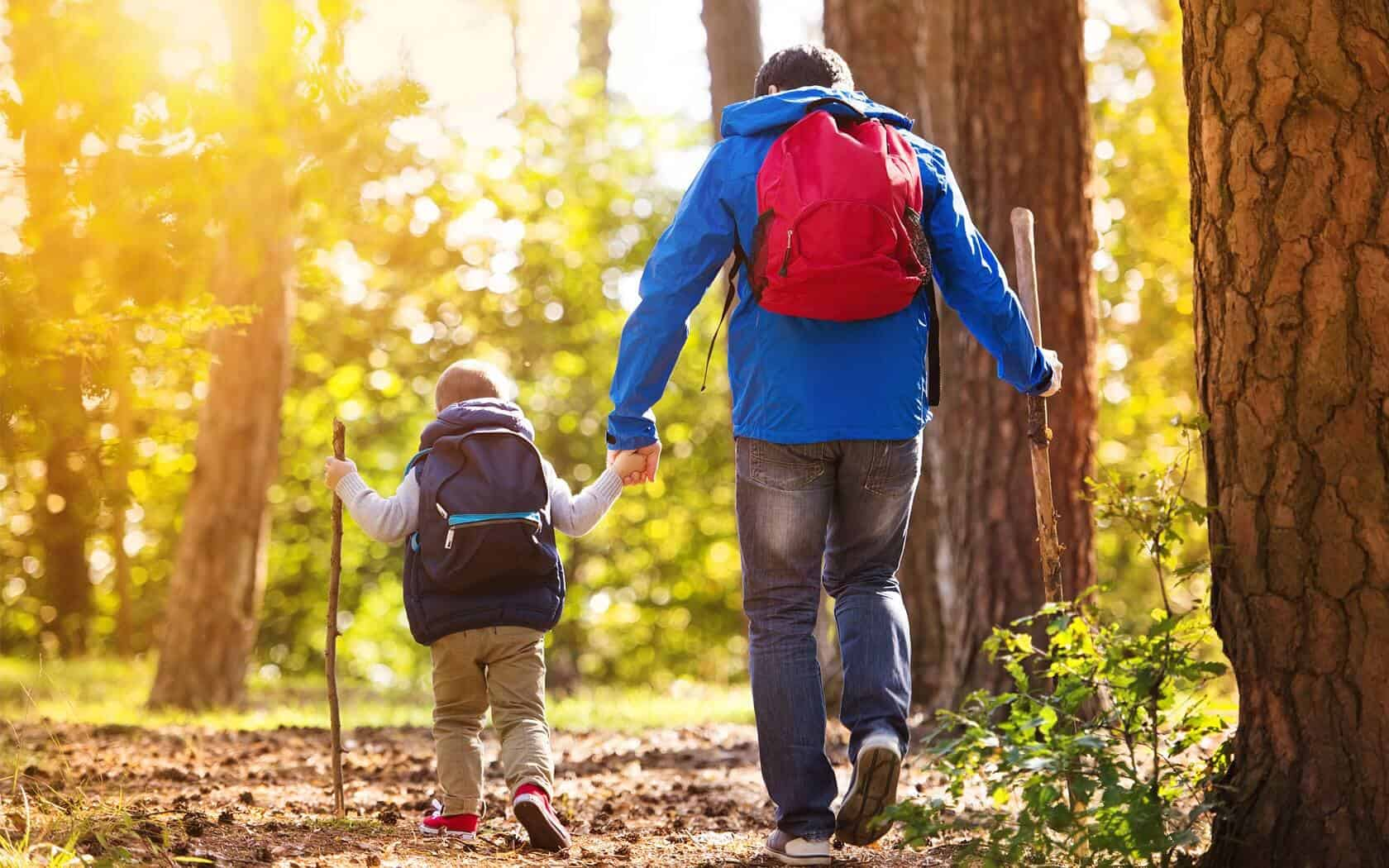 A father and son hiking in the forest.