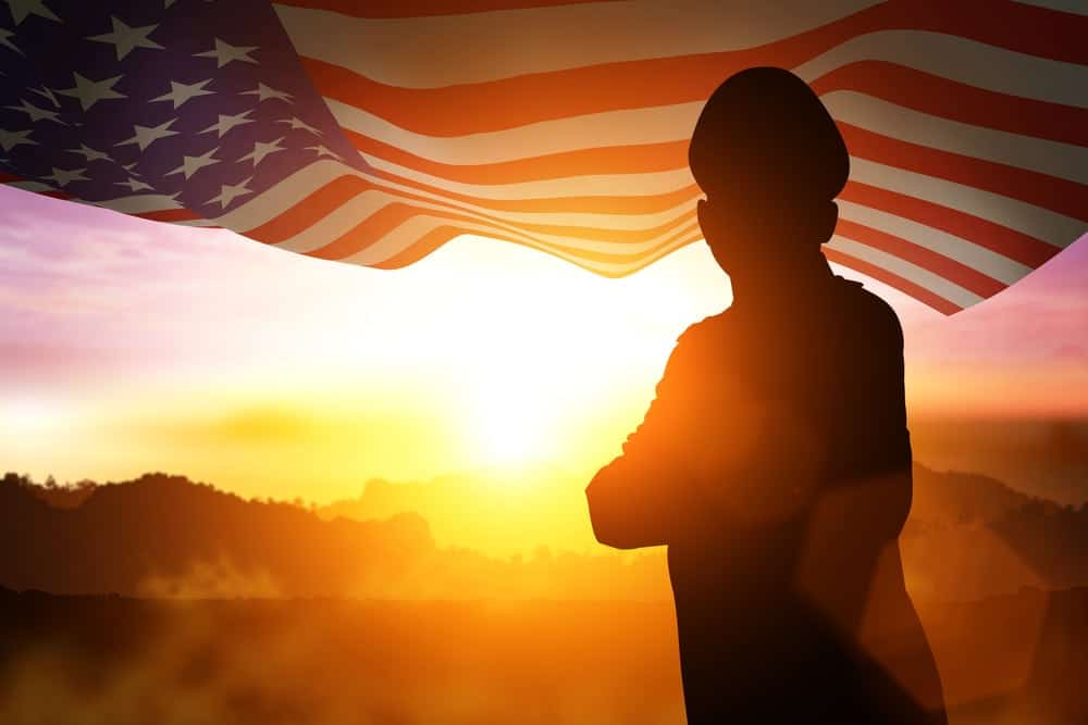 Photo of veteran with sunset over mountains and American flag